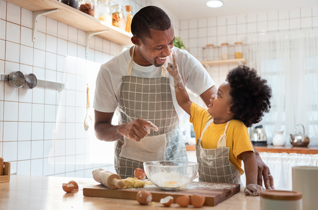 Black father and son having fun while baking cookies at home together.