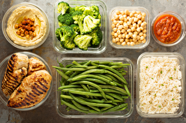 Various bowls and dishes of chicken, vegeteables and rice for meal prepping