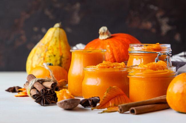 Pumpkins, squash, jars of pumpkin puree and fall spices