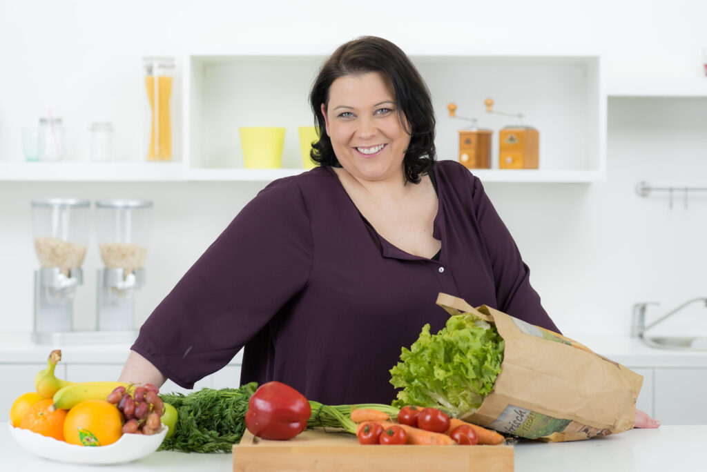 White woman standing in front of counter with fresh produce laid out
