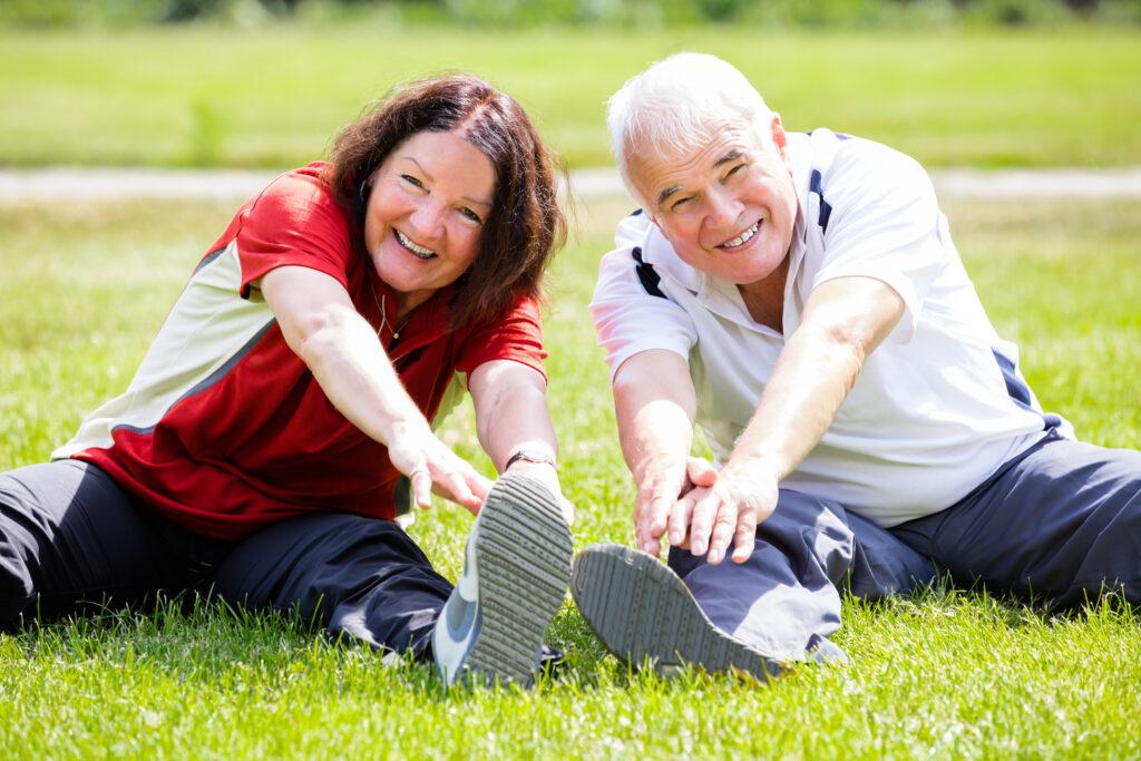 Smiling Senior Couple Doing Fitness Exercise In Park