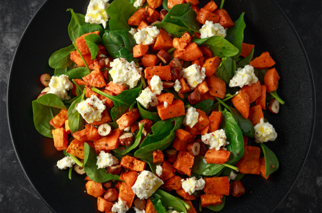 Healthy roasted sweet potato salad with spinach, feta cheese, and nuts on a black plate