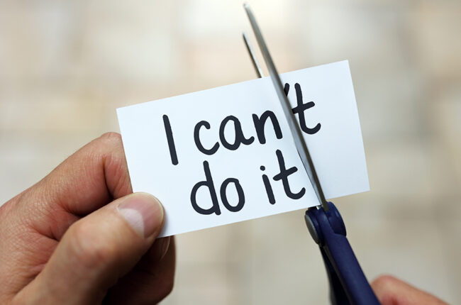 """Hand holding a piece of paper that says """"I can't do it"""" with scissors cutting off the """"'t"""" so it say """"I can do it"""""""