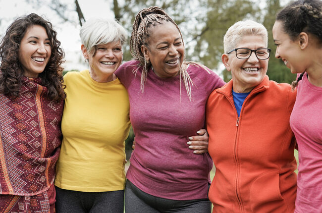 Diverse group of women hugging side by side outside