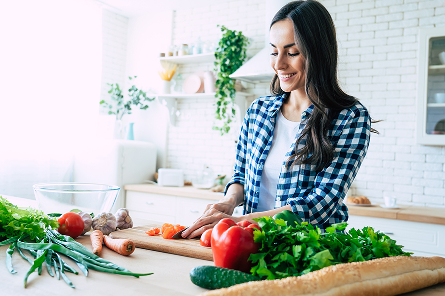 Women smiling in kitchen chopping vegetables