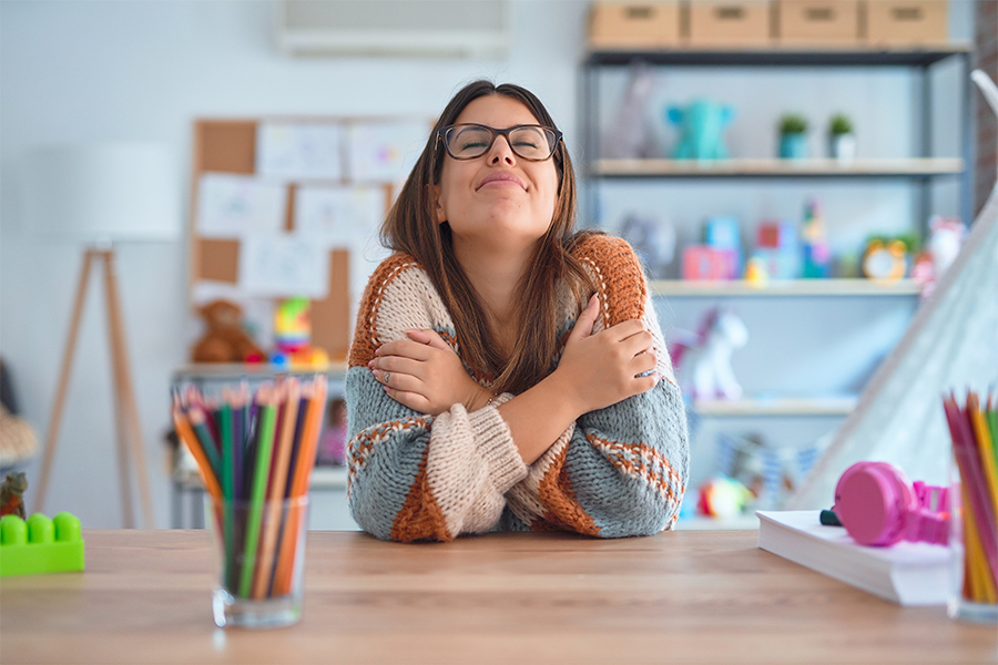 Female teacher in classroom, sitting at desk and hugging herself and smiling with eyes closed