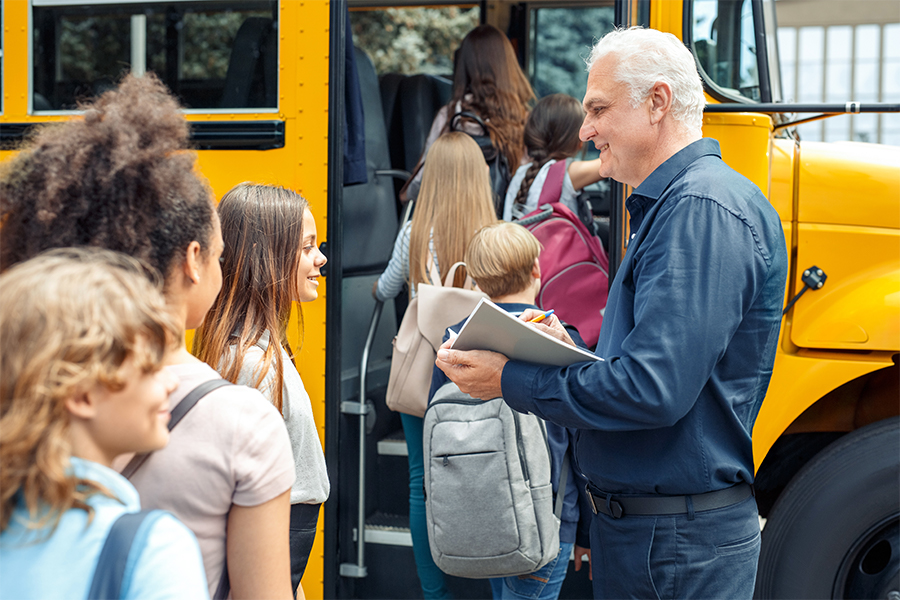 Bus driver taking a head count as children get on the school bus.