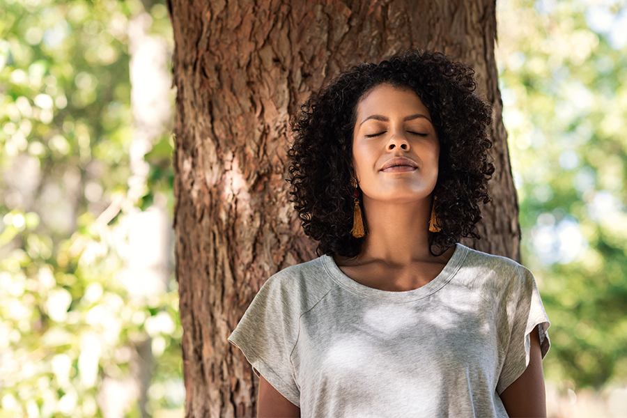 Black woman standing in front of tree, eyes closed, meditating