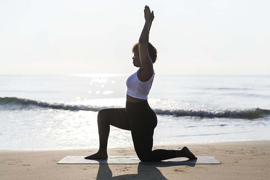 Black woman doing yoga at the beach