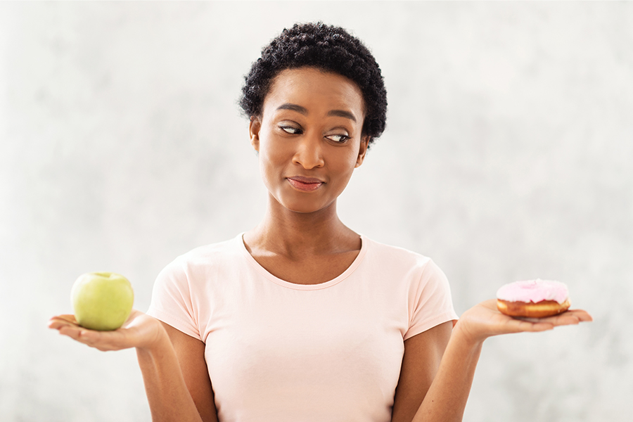 Black lady holding apple and donut in her hands, tempted to eat dessert instead of fruit