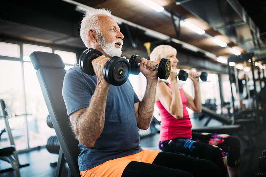 Happy senior couple doing exercises in gym to stay fit