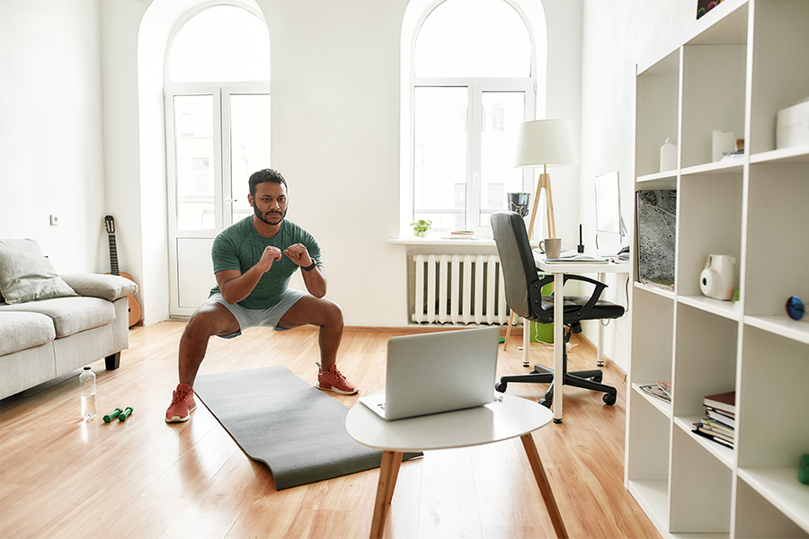 Indian man in living room watching a video on his computer and working out, squatting