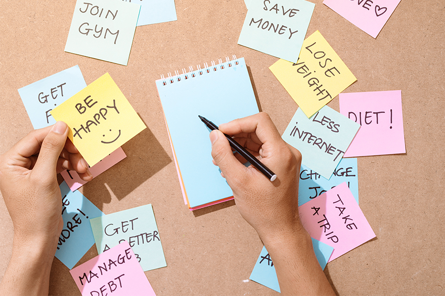 Hands about to write in a notebook with sticky notes all over listing resolutions