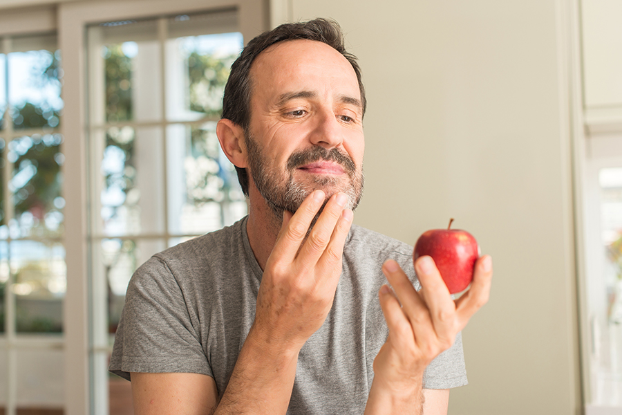 Middle age man holding and looking at red apple with serious face, thinking