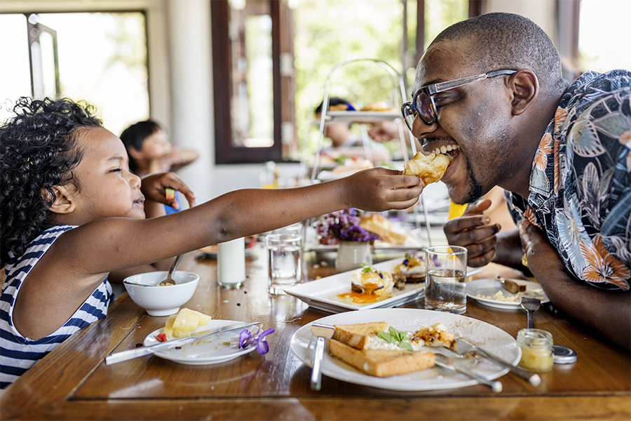 Black family father and daughter having breakfast at hotel restaurant