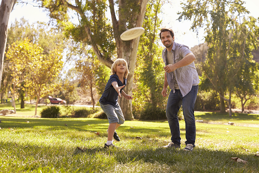 Father and son playing frisbee in the park