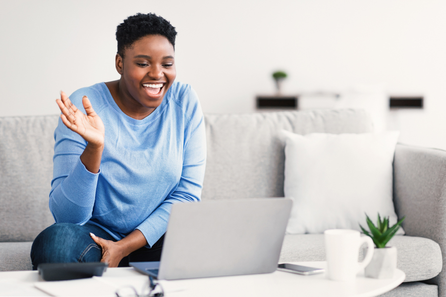 Black woman sitting on couch waving hello to someone on zoom