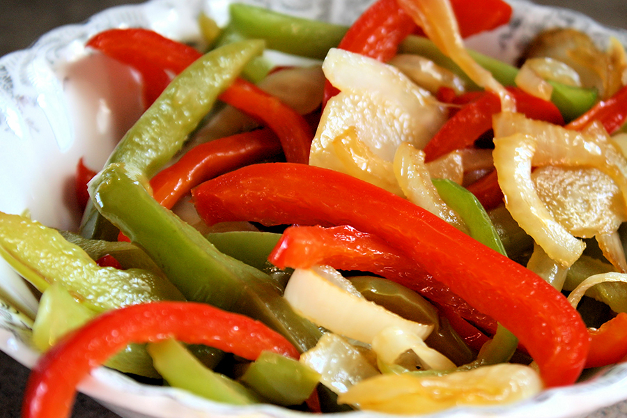 Close up of cooked red and green bell peppers and onions