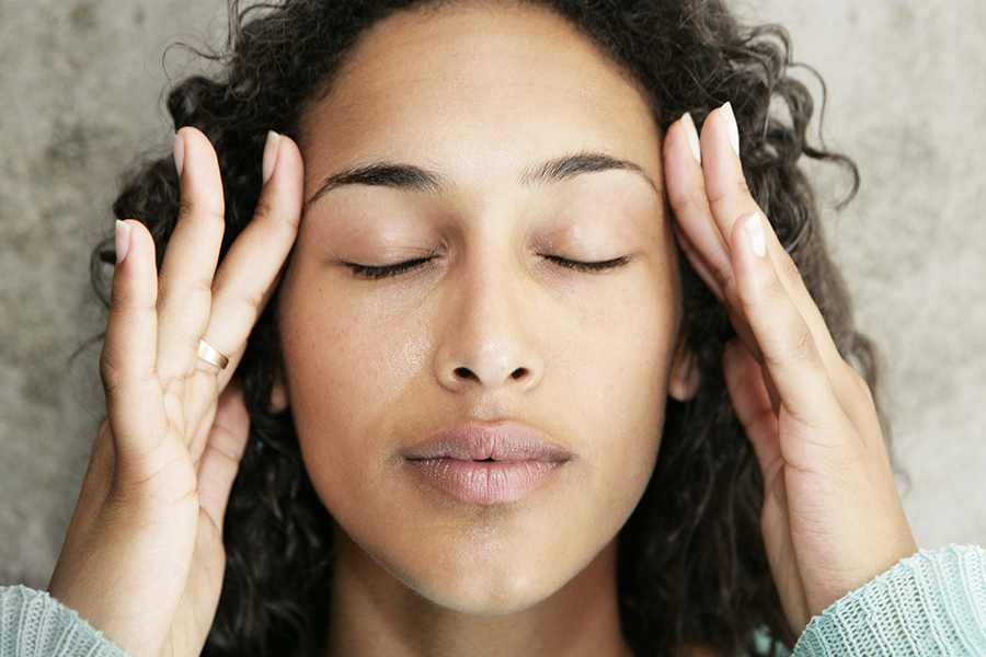 Woman rubbing sides of forehead to relax