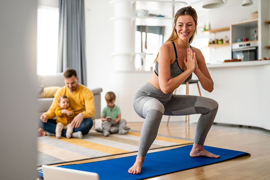 Mom working out in living room with dad and kids playing behind her
