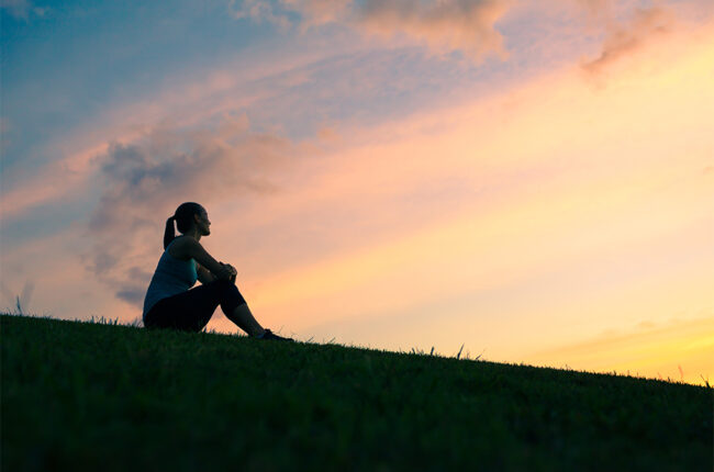 Woman sitting on hill at sunset thinking