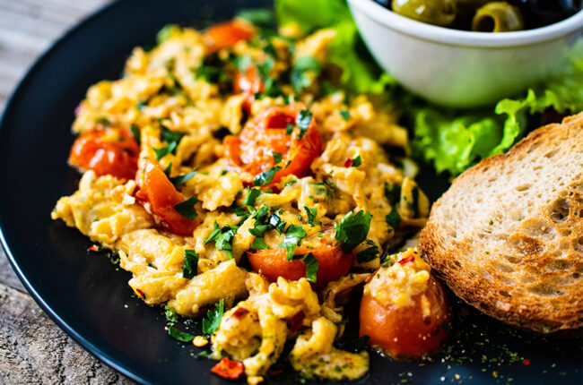 Scrambled eggs with tomatoes on a plate with bread and a bowl of olives