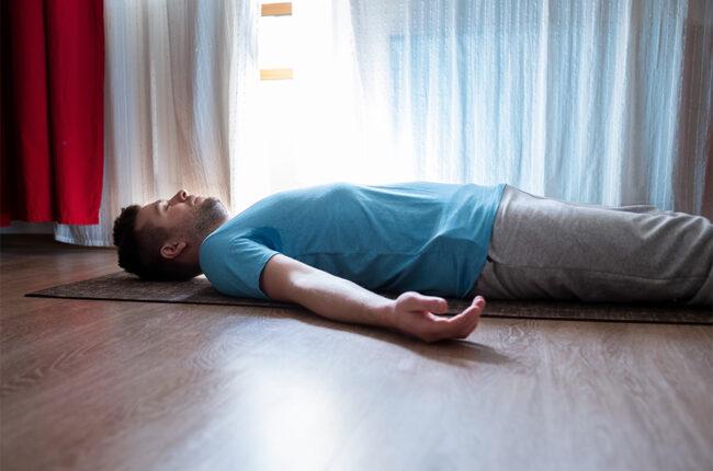 Man laying on yoga mat, yoga nidra