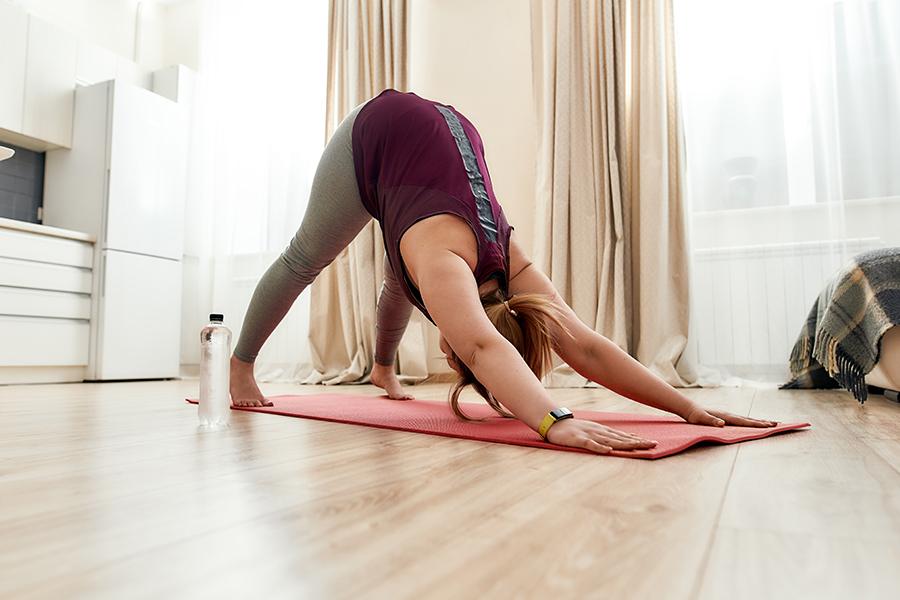 Woman doing downard dog yoga pose at home