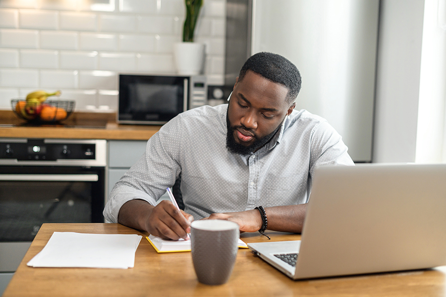 Hard-working African American man sitting at the table at home in the modern kitchen, using the laptop for distance video communication, studying, working, meeting online, and making notes