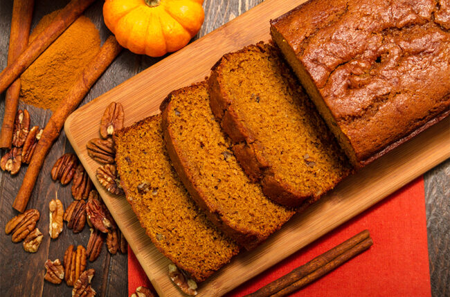 Pumpking bread slices and loaf on a cutting board with walnuts scattered around