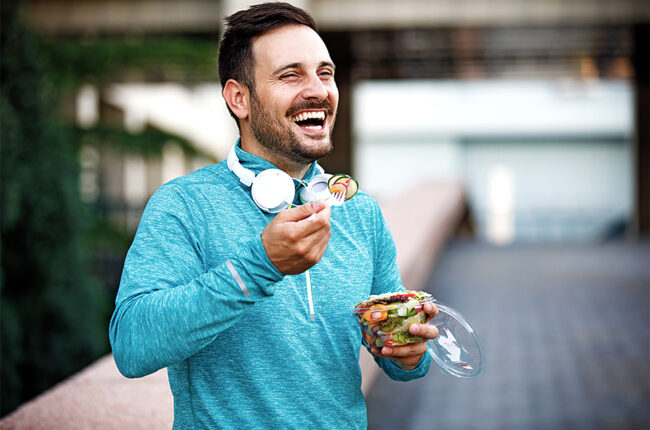 Man in workout clothes outside eating a salad and smiling
