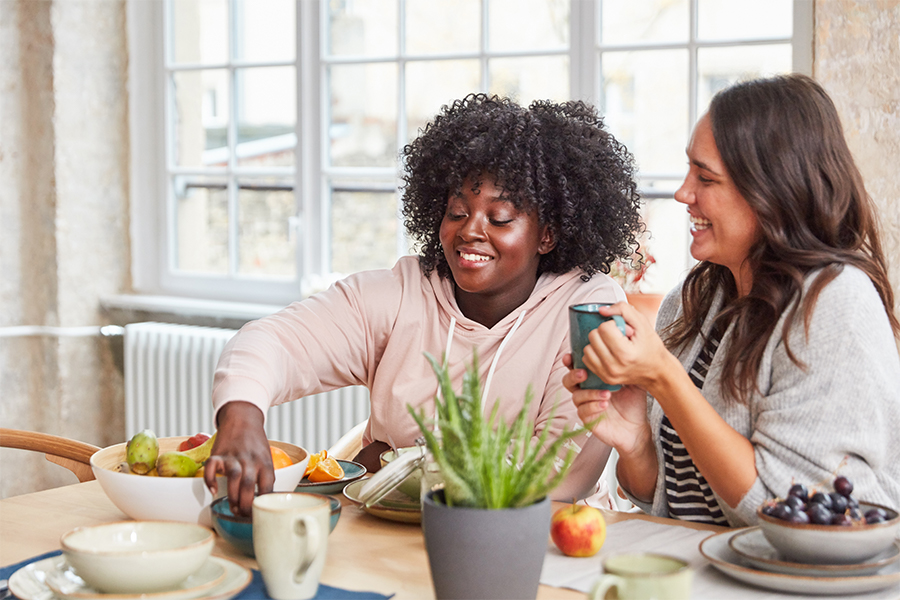 2 women eating fruit at dining table and chatting
