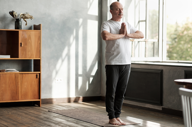 Sporty senior hispanic man in a basic standing asana tadasana, mountain yoga posture at home.