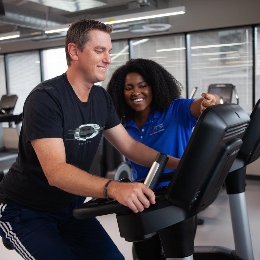 Coach helping man on exercise bike
