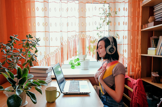Female in headphones sits at front of laptop and breathing.