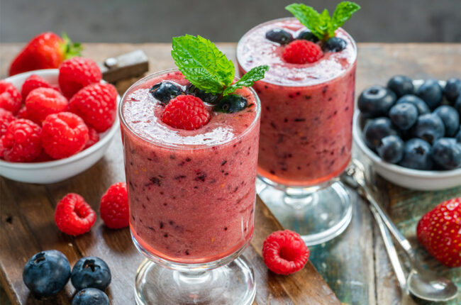 2 glasses of Berry Antioxidant Smoothie with raspberries and blueberries aroud them