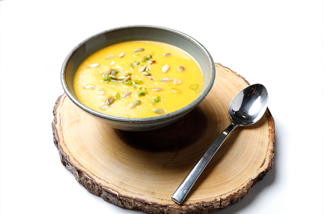 Bowl of Smoky Sweet Potato Soup with Pumpkin Seeds on a tree stump placemat