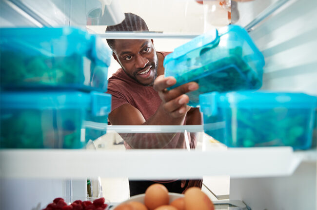 View looking out from inside of refrigerator as a Black man takes out healthy packed lunch in container
