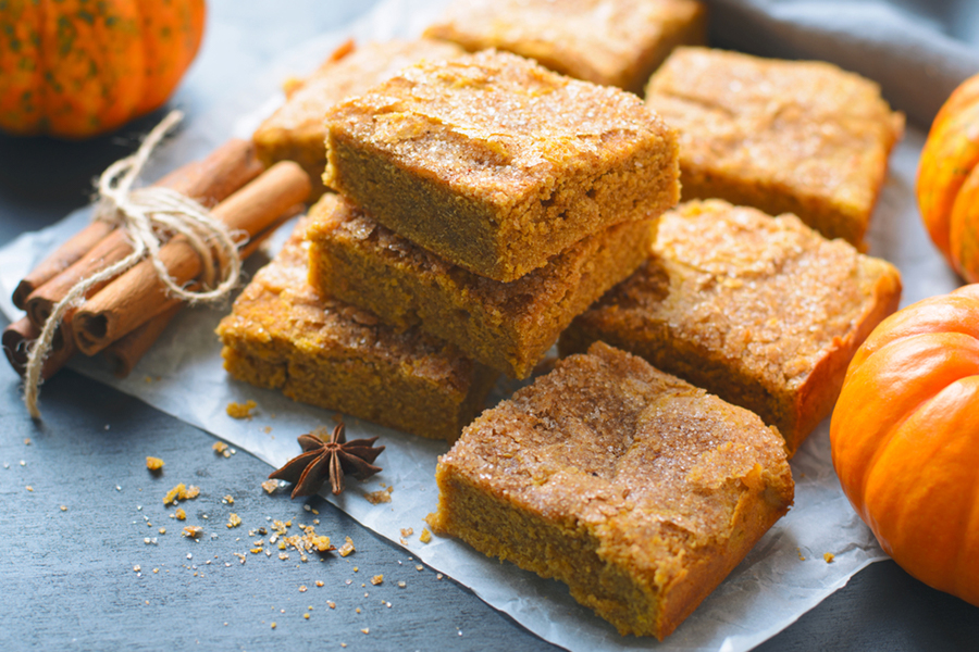 Stack of Pumpkin Spice Protein Squares with pumpkins and cinnamon sticks