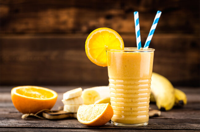 Glass of Mango Orange Creamsicle Smoothie with orange slice garnish