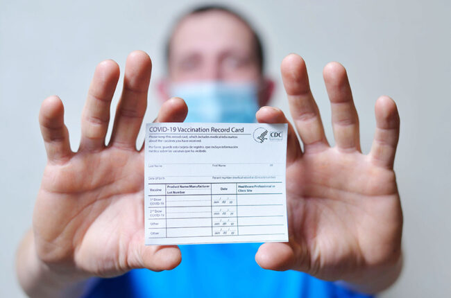 Man holds out COVID-19 vaccination record card