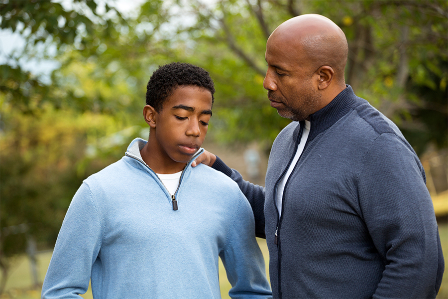 African American father and son deep in conversation