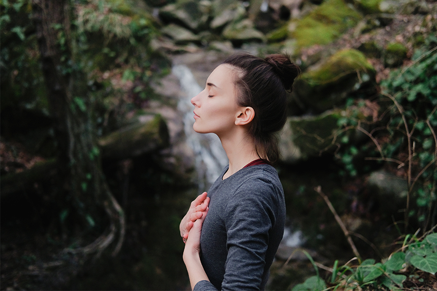 Women standing in forest, hands over heart, eyes closed, meditating