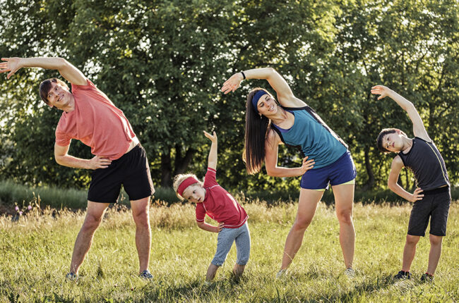 Mom, dad and 2 young boys outside stretching in workout clothes