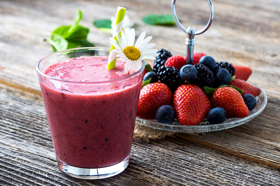 Cup of berry smoothie next to plate of fresh berries