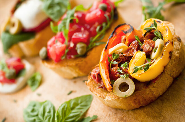 Bread slices topped with roasted bell peppers and tomatoes