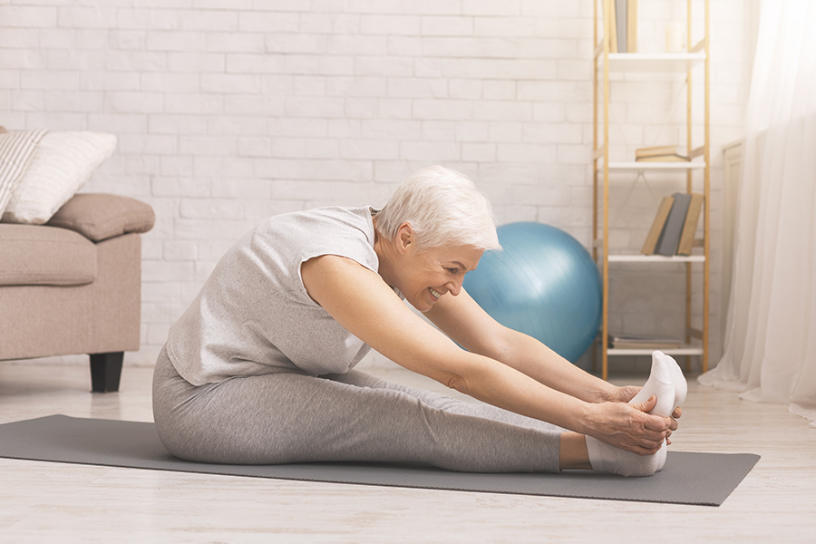 Eldery woman sitting on yoga mat reaching for her toes stretching
