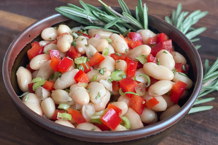 Bowl of white beans, tomatoes and rosemary sprigs